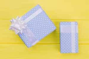 Blue gift boxes on yellow background. Present boxes packed in light blue patterned paper on color table. New Year or Christmas gifts.